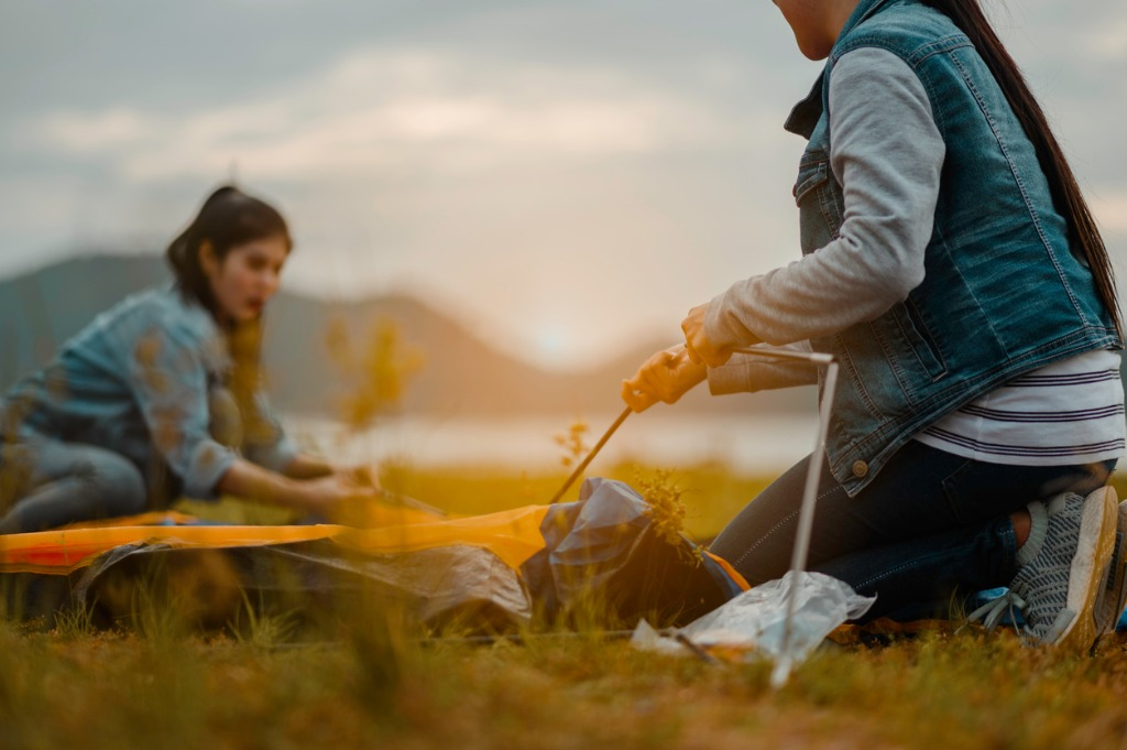 two-women-pitching-tents-for-camping-on-camping-holiday-picture-id1189876417